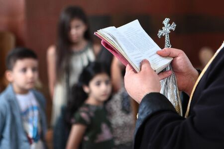Photo pour The hands of a priest in an Armenian church hold a book and a cross. The text and faces of the children are out of focus. Photo without a face in the interior. Concept of religion and service to God. - image libre de droit
