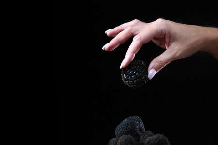 Photo pour Black truffle in the woman's hand. Exquisite and fragrant mushroom. Unrecognizable person. Dark background. Close up. Copy space. - image libre de droit