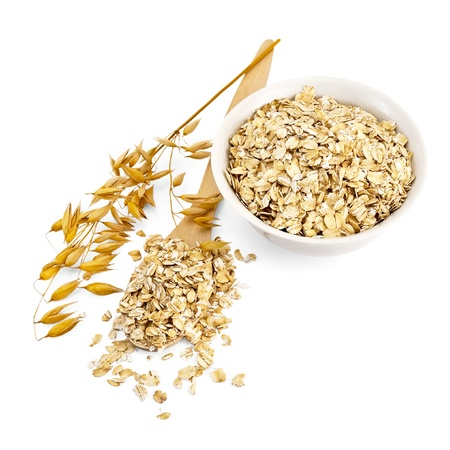 Rolled oats in a wooden spoon and a white porcelain bowl, oat stalks isolated on white background