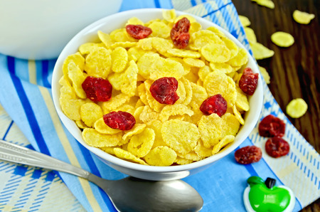 Yellow corn flakes with dried cherries, milk in a jug, spoon, napkin on the background of wooden boards