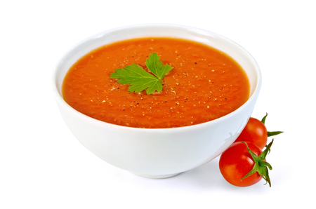 Tomato soup in a white bowl with parsley and tomatoes isolated on white backgroundの写真素材