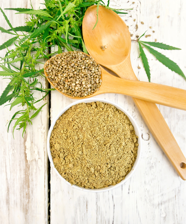 Hemp flour in bowl, grain in spoon, cannabis leaves on the background of the wooden boards top