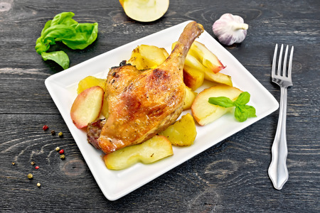 Roasted duck leg with apple, potatoes in a rectangular white plate, basil, garlic and fork on black background wooden plank