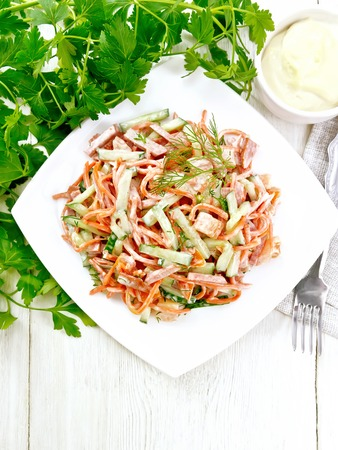 Photo pour Salad from smoked sausage, spicy carrot, tomato, cucumber and spices, dressed with mayonnaise, napkin, fork and parsley on the background of a light wooden board from above - image libre de droit