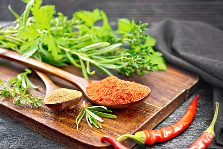 Photo for Ground hot red pepper and paprika in spoons, chili pods, spicy greens and a napkin on wooden board background - Royalty Free Image