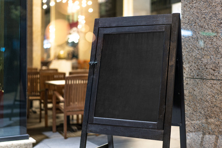 Photo pour Close up of black sandwich board next to restaurant. - image libre de droit
