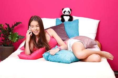 natural young woman making a call in her pink room