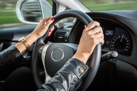 Woman's hands on the steering wheel of the car