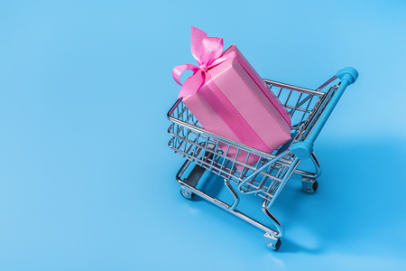 Shopping cart with gifts in pink smart box.