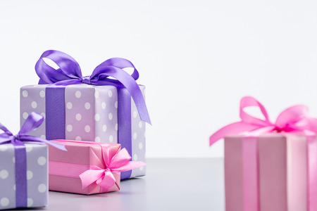 Foto de Gift boxes, in pink and violet in polka dot packaging, decorated with ribbons and bows. - Imagen libre de derechos