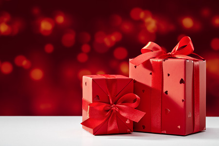 Photo for Surprise in red box with bow on bokeh background. Festive design, on white table. Copy space. - Royalty Free Image