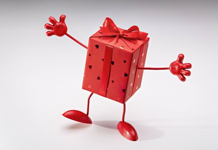 Photo for Gift in box. Red box on legs, with hands. Cartoon figure. Copy space. - Royalty Free Image