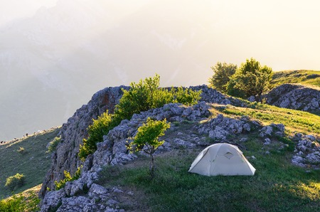 Spring landscape with tourist tent Camping in the mountains of the Solar spring day