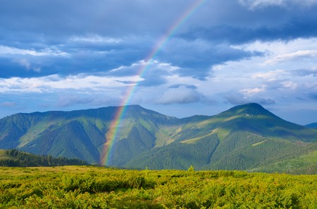 Foto de Summer landscape with a rainbow in the mountains  Sunshine after the rain  Beauty in nature - Imagen libre de derechos