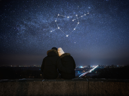 Foto per Valentines Day card. Couple in love looking at stars. Night in city. Constellation in shape of a heart - Immagine Royalty Free