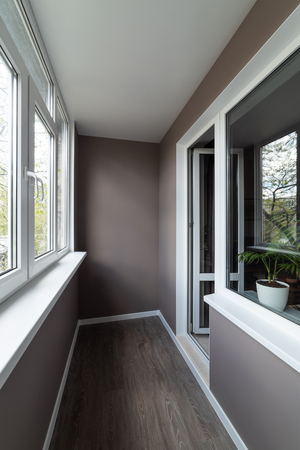 Balcony after repair. Walls with wallpaper are painted in brown