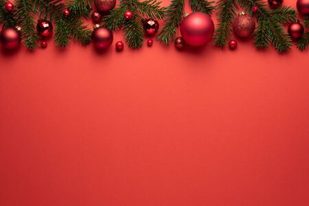 Foto de Red background with Christmas balls and fir branches. Merry Christmas or New Year decoration with copy space - Imagen libre de derechos