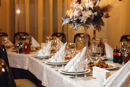 Photo pour The table setting empty wineglasses on white tablecloth. Selebration banquet with white napkins, plates and wineglasses for white and red wine on the white table in restaurant - image libre de droit