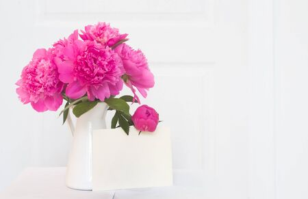 Photo for Pink peonies in white enamelled vase. Beautiful flowers in interior design. White paper for invitation text, white peonies in a vase, interior decoration. - Royalty Free Image