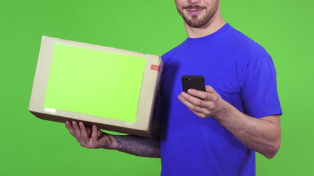 Cropped shot of a handsome bearded cheerful deliveryman delivering order to the customer holding cardboard box with copyspace using smart phone typing messages service concept.
