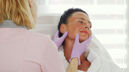 Foto de Beautiful mature woman getting her skin examined by professional dermatologist. Cosmetologist examining face of her female client before providing treatment. Dermatology, skincare concept. - Imagen libre de derechos