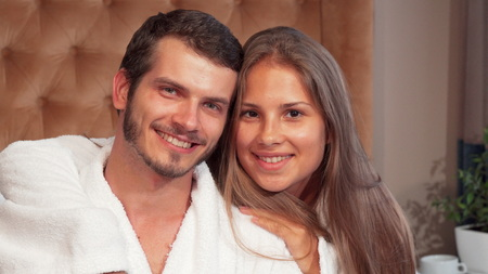 Happy couple embracing smiling to the camera together. Beautiful young woman embracing her husband in the bedroom. Loving couple wearing bathrobes smiling to the camera at their honeymoon suite. Love, travel, marriage, romance concept.