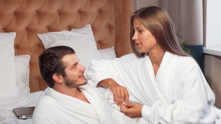 Beautiful couple relaxing together in bed, wearing bathrobes. Gorgeous woman smiling, talking to her boyfriend while relaxing at home in bed together. Lovely young couple cuddling at their hotel room, wearing bathrobes. Love, couples, travel concept.