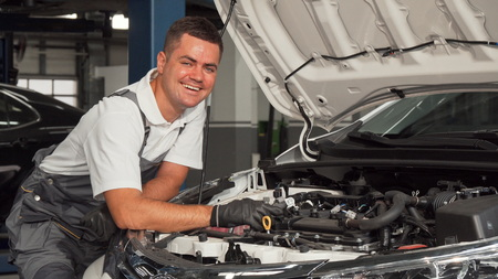 Cheerful mechanic enjoying working at the garage. Young cheerful car mechanic smiling to the camera while examining engine of a car. Professional auto mechanic working at his garage, looking under the hood of a car. Service, driving concept.