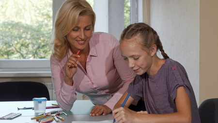 Mature beautiful woman enjoying drawing with her little student. Cute red haired schoolgirl coloring and drawing with the help of her teacher. Profession, job, occupation, teaching concept.