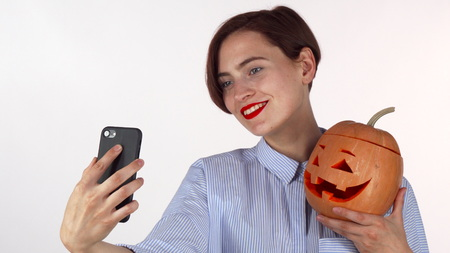 Foto de Beautiful woman taking selfies with Halloween pumpkin. Attractive female with red lips using smart phone, taking photos with carved jack-o-lantern isolated. Technology concept - Imagen libre de derechos