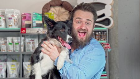 Photo for Happy man holding his adorable dog, smiling to the camera. Cheerful bearded man cuddling with his cute dog at vets office. Healthy happy canine, dogs, family concept - Royalty Free Image
