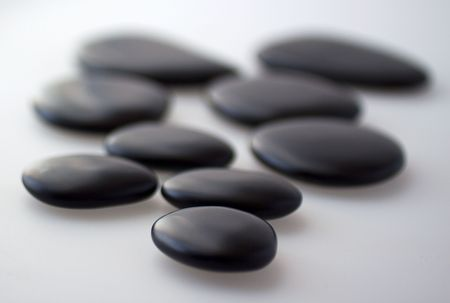 Black basaltic stones for massage over gray background