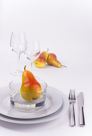 Restaurant table set with plates, pears, wine glasses and silverware for poster