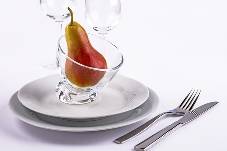 Celebration table set with pear in glass bowl and silverware for menu
