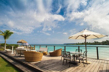 Photo pour Outdoor restaurant at the beach. Cafe on the beach, ocean and sky. Table setting at tropical beach restaurant. Dominican Republic, Seychelles, Caribbean, Bahamas. Relaxing on remote Paradise beach. - image libre de droit