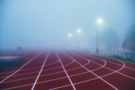 Photo pour Truck and Field concept photo. Red athletics track in morning mist. Running photo,  - image libre de droit