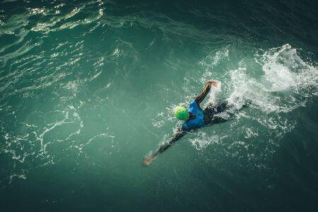 Photo pour Alone swimmer train at sea in dark summer day. - image libre de droit