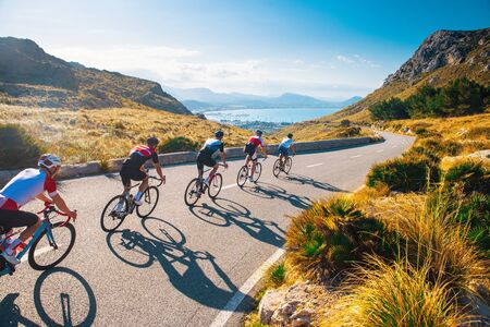 Photo pour Group of cyclist ride together on road bicycles in beautiful nature. Sunset light, sea in background... - image libre de droit
