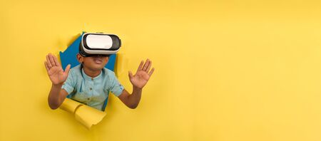 Photo pour African-American boy in virtual reality headset VR. Immersed in virtual 3d world, touches virtual objects, interacts with computer world, on yellow torn paper background with space for text - image libre de droit