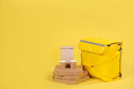 Photo pour Yellow refrigerator bag for food delivery or for trip to nature and tourism on yellow background with food pizza and drinks in an eco-friendly paper packaging. Thermos bag protects food from spoilage - image libre de droit