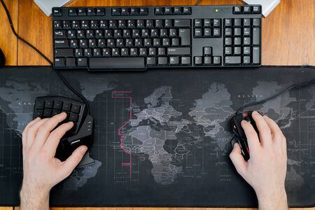 Photo pour one hand on the gaming keyboard, the second on a computer mouse on a background of a computer mat with a world map - image libre de droit
