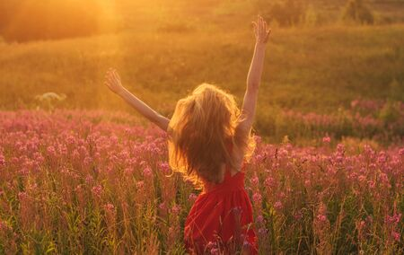 Photo pour Dancing and jumping girl with hands up in red dress among blooming Sally field in sunset - image libre de droit