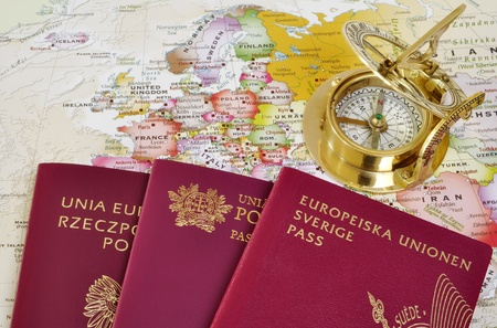 Polish, Portuguese and Swedish passport on a map with old compass