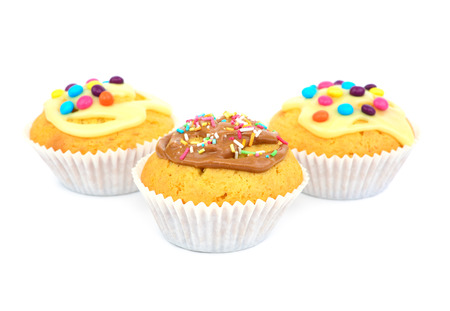 Three cupcakes with candys and glaze isolated on white