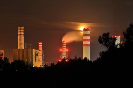 Power lights illuminated at night. Chimneys launching smoke. Cranes, extending the electron. Heat generation. United factory.