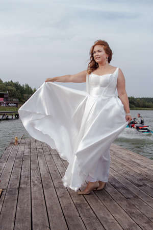 Photo pour Red-haired bride in a white dress posing on a quay near a lake - image libre de droit