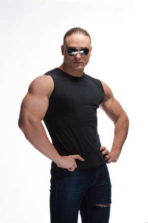 Photo pour Portrait of a brutal man bodybuilder model in sunglasses on a white background - image libre de droit