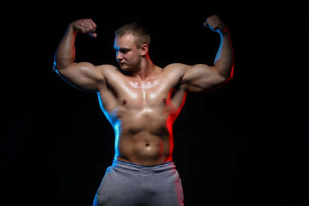 Photo pour male bodybuilder athlete with naked torso posing against a black background, in red and blue light - image libre de droit