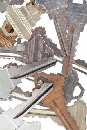 Detailed shot of various metallic keys on white.