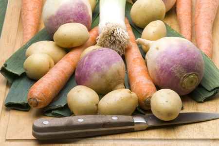 Root vegetables ready for pot roast resting on wood cutting board with paring knife.